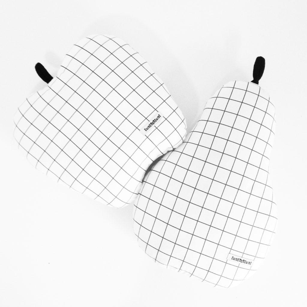 Les coussins minimalistes quadrillés de l'artisane Inkibabinki en forme de poire ou de pomme 49$.